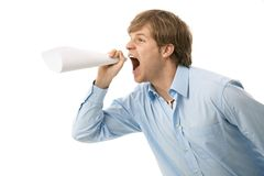 Young man shouting. Through rolled up paper, as if imitating megaphone Stock Images