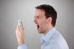 Young Man Shouting. At his mobile phone Stock Photos