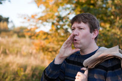 Young man  shouting in autumn forest on sunny day Royalty Free Stock Images