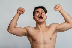Young man shouting. A young man shouting and flexing muscles Stock Images