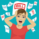 Young man shouting grabbed his head with tax and bill papers. On blue background Royalty Free Stock Photos