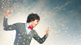 Young man shouting at his mobile phone. Young businessman with a red tie shouting furiously at his mobile phone Stock Photo