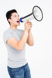 Young man shouting on horn loudspeaker Stock Images