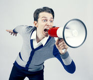 Shouting. Young man shouting into a megaphon Royalty Free Stock Image