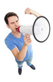 Young man shouting through megaphone. Young man over white background Stock Images