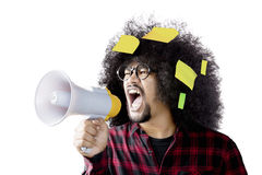 Young man shouting with megaphone. Young afro man shouting by using a megaphone with blank sticky notes over head, isolated on white background Royalty Free Stock Photography