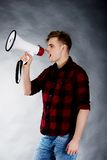 Young man shouting in megaphone. Royalty Free Stock Photo