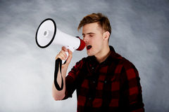Young man shouting in megaphone. Stock Photo