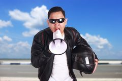 Young Man Shouting with Megaphone, Motivating Concept. Asian motorcyclist biker racer shouting with megaphone, mad yelling screaming crazy supporting motivating Royalty Free Stock Photos