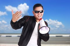 Young Man Shouting with Megaphone, Promotion Concept. Photo image portrait of funny young Asian man shouting with megaphone, mad yelling screaming crazy Royalty Free Stock Photos