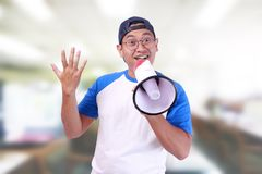 Young Man Shouting with Megaphone, Promotion Concept. Photo image portrait of funny young attractive Asian man shouting with megaphone, happiness excited calling Royalty Free Stock Photography