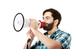Young man shouting through megaphone. Young man yelling into megaphone Royalty Free Stock Image