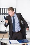 Young man is shouting into the phone. Young businessman is shouting into the phone while standing at the desk in the office. A shelf is in the background. The Stock Images