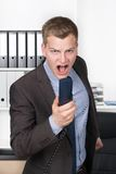 Young man is shouting into the phone Stock Image