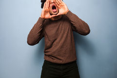 Young man is shouting to get his message across. Young man is standing and shouting to get his message across Royalty Free Stock Photography