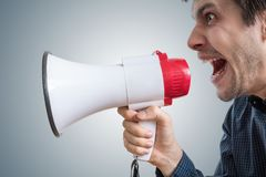 Young man is shouting to megaphone and announcing news Stock Photos