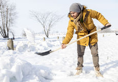 Young man shoveling snow in the country. Young man shoveling snow near a small wood after a big snowfall Stock Photography