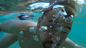 Young man show a thumbs up underwater stock video