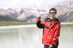 Young man show water bottle in nature. Young man with black glasses show clean water bottle near a lake under snow mountain in nature Stock Photography