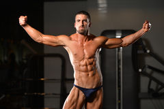 Young Man Showing Abdominal Muscle. Healthy Man Standing Strong In The Gym And Flexing Muscles - Muscular Athletic Bodybuilder Fitness Model Posing After stock photos