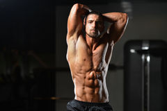Young Man Showing Abdominal Muscle. Healthy Man Standing Strong In The Gym And Flexing Muscles - Muscular Athletic Bodybuilder Fitness Model Posing After stock image
