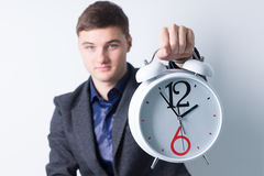 Young Man Showing Alarm Clock at the Camera Royalty Free Stock Images