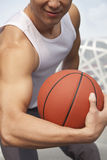 Young man showing bicep and holding basketball Stock Photos