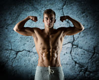 Young man showing biceps and muscles Royalty Free Stock Image