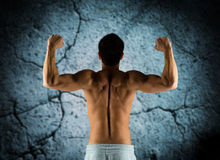 Young man showing biceps and muscles Royalty Free Stock Photos