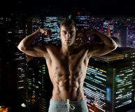 Young man showing biceps and muscles Stock Photography