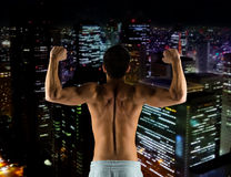 Young man showing biceps and muscles. Sport, bodybuilding, strength and people concept - young man showing biceps and muscles over night city background Royalty Free Stock Photography