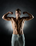 Young man showing biceps Stock Images