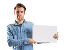 Young man showing a blank paper page. Ready for text or product, two clipping paths included, one for body and second for the page Royalty Free Stock Images