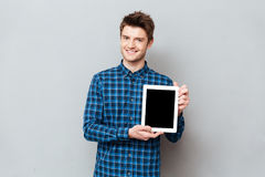 Young man showing blank screen of tablet computer. Young smiling man showing blank screen of tablet computer vertically stock image