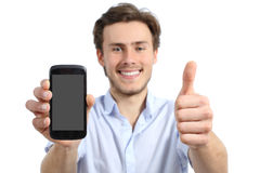 Young man showing a blank smart phone screen with thumbs up. Isolated on a white background Stock Photos