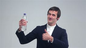Young man showing a bottle of water and shows great stock video