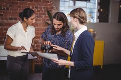 Young man showing camera to female colleagues stock photos
