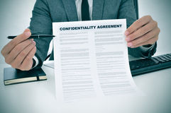 Young man showing a confidentiality agreement document. A young man showing a confidentiality agreement document Royalty Free Stock Images