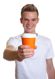 Young man showing a cup of coffee Stock Photos