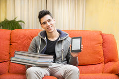 Young man showing difference between ebook reader Stock Photography