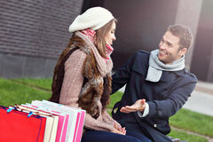 Young man showing disapproval to woman with many shopping bags Stock Image