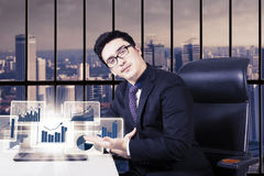 Young man showing financial chart on laptop Royalty Free Stock Photo
