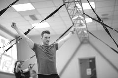 Young man showing fitness exercises in the gym, monochrome Royalty Free Stock Photography