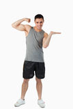 Young man showing his biceps while presenting Stock Images