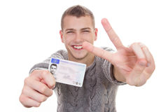 Young man showing his driver license. 16 to 18 year old boy just received his driver license Stock Images