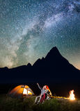 Young man showing his girlfriend stars and Milky way in the night sky Royalty Free Stock Photo