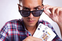 A young man showing his poker pair. Closeup picture of a young man showing his poker pair while looking at you over his sunglasses. On gray background royalty free stock images