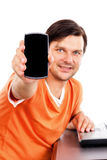 Young man showing his smart phone while sitting at desk Royalty Free Stock Photos