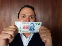 Young man showing and holding a mexican banknote of 500 pesos. Commerce, exchange, trade, trading, value, buy, sell, profit, price, rate, cash, currency, paper royalty free stock photo