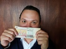 Young man showing and holding an uruguayan banknote of 200 pesos. Commerce, exchange, trade, trading, value, buy, sell, profit, price, rate, cash, currency stock images